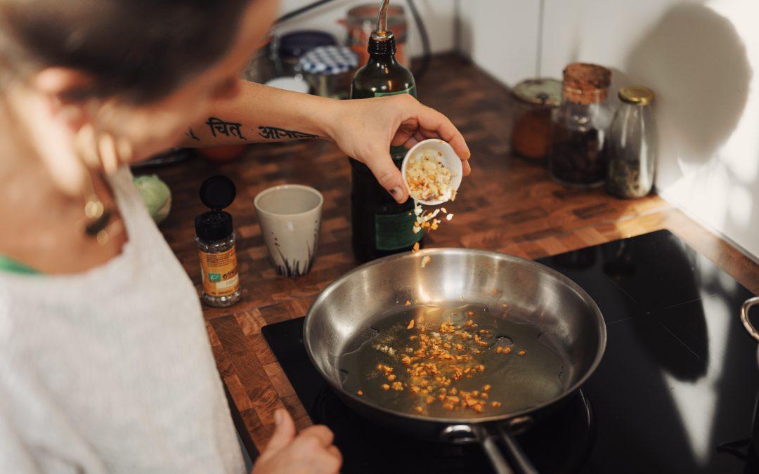 Photo of a woman cooking courtesy Conscious Design via Unsplash.